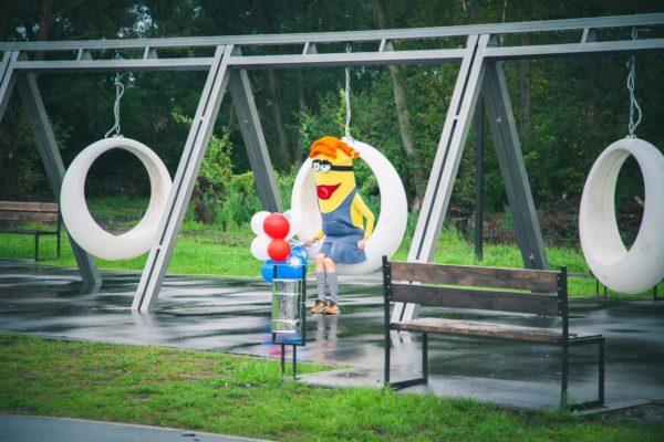 Световые пластиковые качели в парке тройные