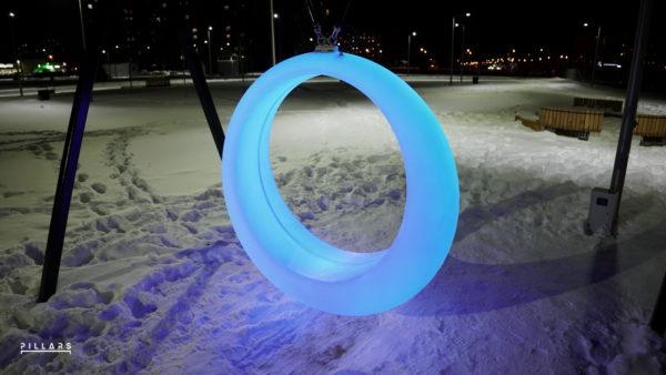 Цветные качели Ring в темноте в парке зимой
